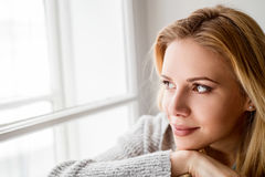Woman sitting on window sill, looking out of window Stock Photos