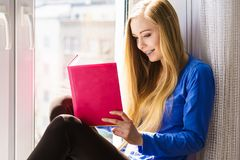 Woman sitting on window sill reading book at home. Leisure, literature and people concept. Young woman teen girl reading book at home while sitting on window royalty free stock photography