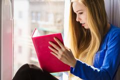 Woman sitting on window sill reading book at home. Leisure, literature and people concept. Young woman teen girl reading book at home while sitting on window stock photos