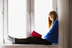 Woman sitting on window sill reading book at home. Leisure, literature and people concept. Young woman teen girl reading book at home while sitting on window stock photography