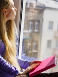 Woman sitting on window sill reading book at home. Leisure, literature and people concept. Young woman teen girl reading book at home while sitting on window stock image
