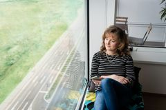Lady at home sitting near window and relaxing Stock Photo