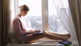 Woman is sitting on the window sill and using her modern laptop. Winter outside the window. Woman is sitting on the windowsill and using her modern laptop stock video footage