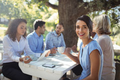 Woman Sitting With Friends In Outdoor Restaurant Stock Photo