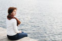 Woman sitting on wood boards by the water Royalty Free Stock Images