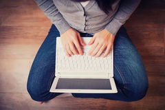 Woman is sitting on wood floor with laptop Royalty Free Stock Photography