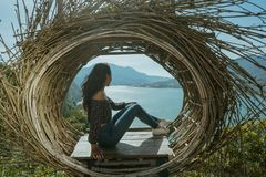 Woman sitting on a wood on top of the mountain. Happy asian woman sitting on a wood on top of the mountain. beautiful nature background stock images