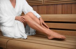Woman sitting on wooden bench. In sauna Stock Photo