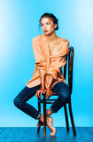Woman sitting on wooden chair in orange shirt on blue background. Fashion, beauty, make up, body art. Woman sitting on wooden chair in orange shirt on blue Stock Photography