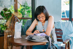Woman sitting on the wooden chair playing mobile phone in casual. Cloths with coffee at cafe Stock Images