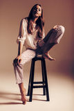 Woman sitting on wooden chair in top and pants Stock Photos