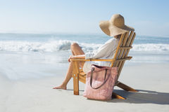 Woman sitting on wooden deck chair by the sea Stock Photography