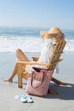 Woman sitting on wooden deck chair by the sea Royalty Free Stock Photography