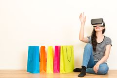 Woman sitting on wooden floor with shopping bags Royalty Free Stock Images
