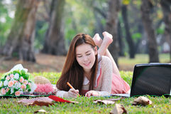 Woman sitting on wooden mat and writing notepad. Royalty Free Stock Photo