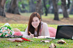 Woman sitting on wooden mat and writing notepad at parkland. Stock Images