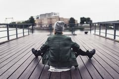 Woman sitting on wooden pier. Back view of stylish woman sitting on wooden pier Royalty Free Stock Images
