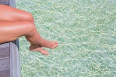 Sexy legs over clear sea water. Tropical beach banner background Stock Photos