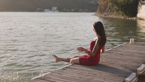 Woman sitting on wooden pier, splashes with her feet in lake water, slow motion. Young woman in red dress sitting on wooden pier, splashes with her feet in water stock footage