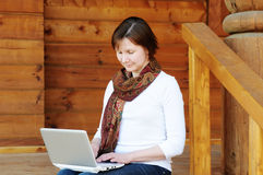 Woman sitting on wooden porch Royalty Free Stock Images