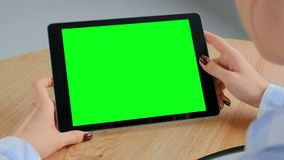 Tablet computer with blank green screen in woman hands - chroma key concept. Woman sitting at wooden table and looking at black digital tablet computer device stock footage