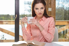 Woman sitting by wooden table and reading book Royalty Free Stock Image