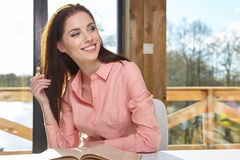 Woman sitting by wooden table and reading book Stock Photography