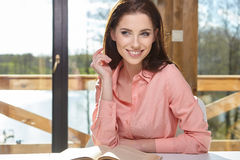 Woman sitting by wooden table and reading book Royalty Free Stock Photography