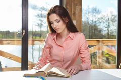 Woman sitting by wooden table and reading book Royalty Free Stock Photo