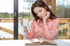 Woman sitting by wooden table and reading book Stock Photos