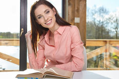 Woman sitting by wooden table and reading book Stock Image