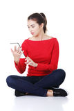 Woman sitting and working on tablet computer, Royalty Free Stock Image