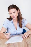 Woman sitting writing at a table Royalty Free Stock Image