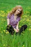 Woman sitting among yellow flowers Royalty Free Stock Image