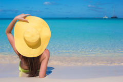 Woman sitting in yellow hat on white sand beach. Young woman sitting in yellow hat on white sand beach enjoying summer vacation Royalty Free Stock Images