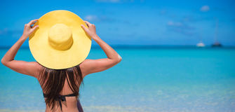 Woman sitting in yellow hat on white sand beach. Young woman sitting in yellow hat on white sand beach enjoying summer vacation Stock Photography