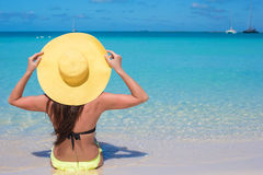 Woman sitting in yellow hat on white sand beach. Young woman sitting in yellow hat on white sand beach enjoying summer vacation Royalty Free Stock Photos