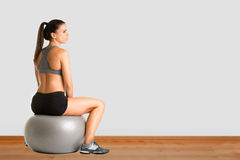 Woman Sitting on a Yoga Ball Royalty Free Stock Photos