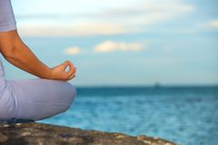 Woman sitting in yoga lotus pose Stock Photography