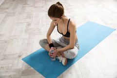 Woman sitting on the yoga mat with bottle of water Royalty Free Stock Photo