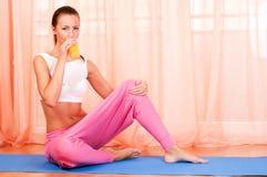 Woman sitting on a yoga mat drinking orange juice Royalty Free Stock Photo