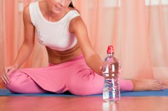 Woman sitting on a yoga mat drinking water Royalty Free Stock Image
