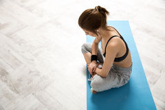 Woman sitting on the yoga mat Royalty Free Stock Photos