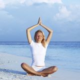 Woman sitting in yoga pose on beach Royalty Free Stock Photo