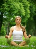 Woman sitting in yoga pose meditation outdoors Royalty Free Stock Image