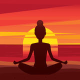 Woman sitting in yoga pose padmasana on the beach. Girl meditating in lotus pose at sunset - peace of mind concept Royalty Free Stock Image
