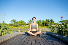 Woman sitting in yoga pose at park Stock Image
