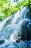 Woman sitting yoga pose in spiritual relaxation serenity and meditation at stunning beautiful waterfall and rain forest in Bali Su. Attractive woman sitting yoga stock photo