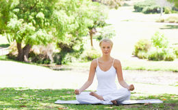 Woman sitting in a yoga position Royalty Free Stock Photo