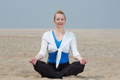 Woman sitting in yoga position at the beach. Mature woman sitting in yoga position at the beach Royalty Free Stock Photography